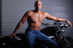 Man and motor cycle. Hot mixed race man wearing jeans and no shirt sitting on a motor cycle stock photos