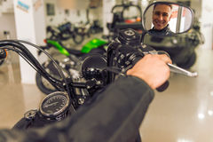 Man with motorbike. Attractive young blond man in black leather jacket is looking at his reflexion in motorbike mirror and smiling Royalty Free Stock Photography