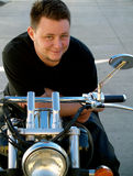 Man on a motorcycle. Happy man leaning on his bike Stock Images