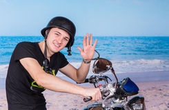 Man on Motorcycle at Beach Waving at Camera Stock Image