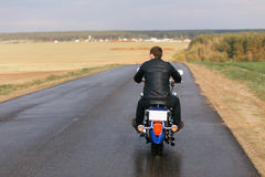 Man on motorcycle. Going away on an empty road royalty free stock photography