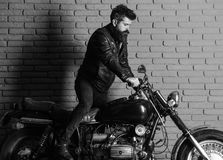 Man on a motorcycle. Hipster, brutal biker on serious face in leather jacket gets on motorcycle. Man with beard, biker. In leather jacket near motor bike in Stock Photography