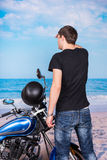 Man with Motorcycle Looking into Distance on Beach Royalty Free Stock Images