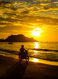Man on a motorcycle rides. A man on a motorcycle rides on the beach at sunset Stock Photo
