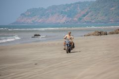A man on a motorcycle rides on a deserted wild beach. Backdrop of mountains and sea Royalty Free Stock Photos