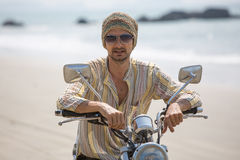 The man on a motorcycle. A man riding a motorcycle on the beach Stock Images