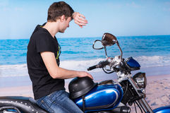 Man on Motorcycle Wiping Forehead at Beach Stock Image