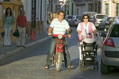 Man on motorcycle and woman with baby in village in Southern Spain off highway A49 west of Sevilla Stock Photo