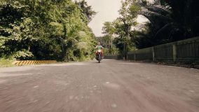 Man motorcyclist driving on motorbike on countryside road on palm trees background. Senior motorcycle rider driving on.  stock footage
