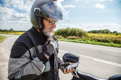 Man motorcyclist in protective helmet looking at smartphone disp Royalty Free Stock Images