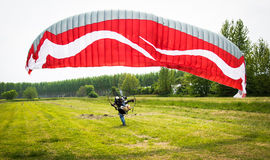 Man with motorized paraglider takes off from a field Stock Images