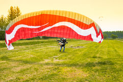 Man with motorized paraglider takes off from a field Royalty Free Stock Image