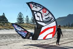 A kite surfer standing on the beach with his kite stock images