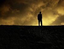 Man on a mountain. Man standing on a mountain at sundown, looking at bottomless hole Royalty Free Stock Images