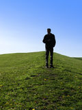 Man on a Mountain. Sillouette of a man standing on a mountain on a clear day Stock Photography