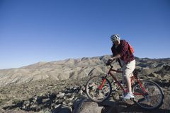 Man With Mountain Bike In An Arid Landscape. Full length of men with mountain bike in an arid landscape looking back his over shoulder Royalty Free Stock Photography