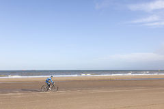 Man on mountain bike on beach with blue sky Royalty Free Stock Photo