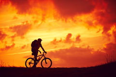Man mountain bike pleasure red clouds Royalty Free Stock Images