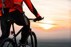 Man on mountain bike rides on the trail on a beautiful sunset. Bicycle wheel closeup. Stock Image