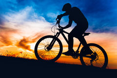 Man on mountain bike at sunset, riding bicycle on hills Stock Photo