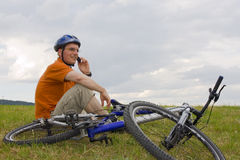 Man with mountain bike talking on cell phone royalty free stock image