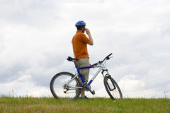Man with mountain bike talking on cell phone Royalty Free Stock Images