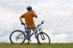 Man with mountain bike talking on cell phone Stock Images