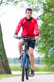 Man on mountain bike in the woods cycling Royalty Free Stock Image