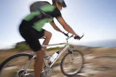 Man mountain biking over extreme terrain, side view, sea in background (blurred motion) Royalty Free Stock Photo