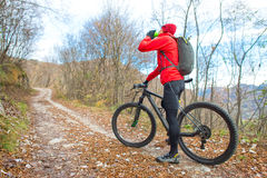 Man mountain biking rests and drinks from the canteen Stock Image