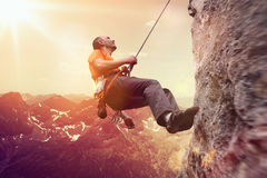 Man mountain climbing a precipitous rock face. Backlit by a glowing sun over alpine mountain peaks Royalty Free Stock Photo