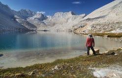 Man on Mountain Lake Shore. Man standing on sierra mountain lake shore looking at landscape Royalty Free Stock Image
