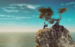 Man on a mountain overlooking the sea Royalty Free Stock Images