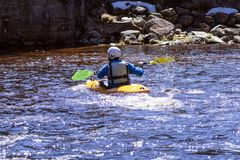A man on a mountain river is engaged in rafting. A girl is kayaking down a mountain river.girl in a kayak, side view royalty free stock images