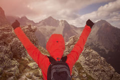Man at mountain summit with hands up Stock Photo