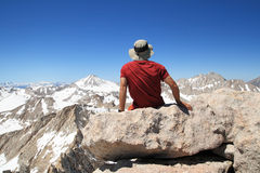 Man on mountain top. Back view of a man sitting on Feather Mountain top enjoying the view Stock Photo