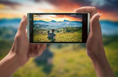 Man in a mountain valley on smartphone screen royalty free stock image