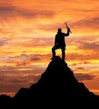 Man on mountains with ice axe in hand Stock Images