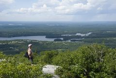 Man in the Mountains of northern Ontario. A male hiker stands on a ridge overlooking the wilderness of northern Ontario in Killarney Provincial Park Stock Images