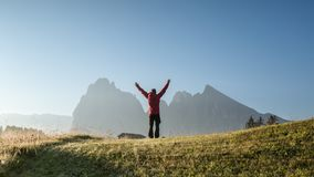 A man in the mountains with raised hands stock images