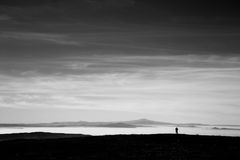 A man in a mountains scenery, looking at a valley filled by fog. And beneath a big, deep sky Royalty Free Stock Photos