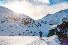 A man in the mountains. Ski touring on a split snowboard. A man stands with his back to the viewer and looks at the mountain royalty free stock image