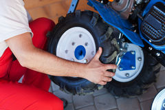 Man mounting tyre on a gasoline motor  tiller Royalty Free Stock Image