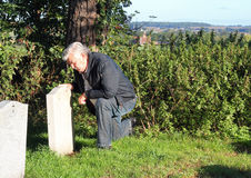 Man mourning at a cemetery. A senior man kneeling beside a headstone and mourning a relative who has died Royalty Free Stock Images