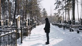 Man mourns or grieves for the dead man in cemetery or graveyard in winter in forest. Place where the remains of dead people are buried or otherwise interred, old stock footage