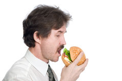 Man with moustache eats hamburger Royalty Free Stock Photo