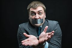 Man with mouth covered by masking tape Stock Image