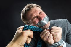 Man with mouth covered by masking tape. Man in capture with mouth and hands covered by masking tape preventing speech, isolated on black Stock Photos