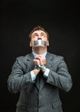 Man with mouth covered by masking tape. Man with mouth and hands covered by masking tape preventing speech, isolated on black Stock Photos