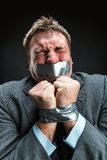 Man with mouth covered by masking tape. Man with mouth and hands  covered by masking tape preventing speech, studio shoot Stock Photos